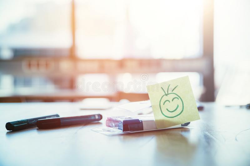 Feedback, motivation and workshop concept: Smiley Illustration on a working place, pens and window in the background. Smiley illustration at the working place royalty free stock photos