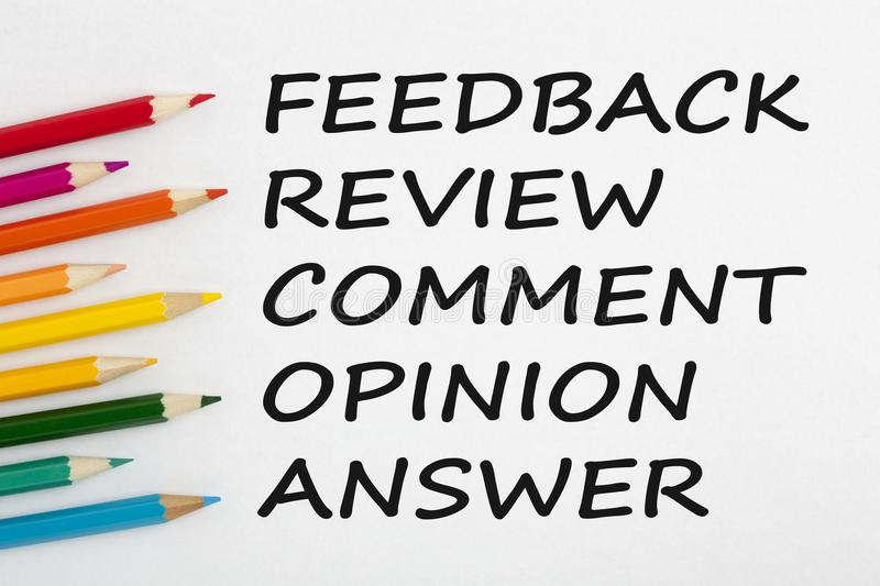Feedback review comment opinion answer concept words. Feedback, review, comment, opinion or answer written on a white background and colour pencils. Business stock image