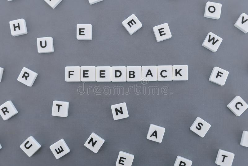 Feedback word made of square letter word on grey background. Survey review text communication evaluation opinion business report customer message concept stock photos