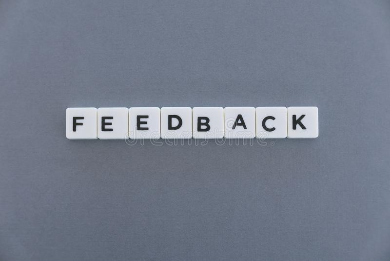 Feedback word made of square letter word on grey background. Survey review text communication evaluation opinion business report customer message concept stock photography