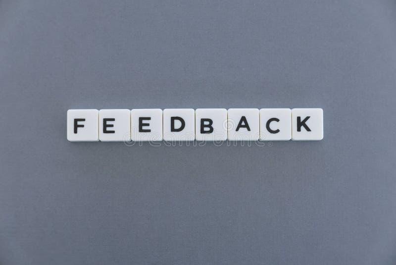 Feedbackwort gemacht vom quadratischen Buchstabewort auf grauem Hintergrund stockfotografie