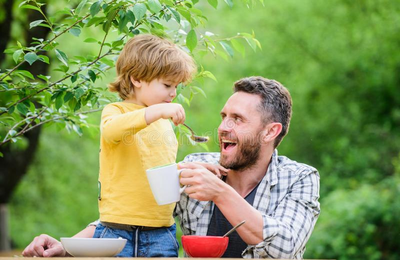 Feeding baby. Menu for children. Family enjoy homemade meal. Father son eat food and have fun. Food habits. Little boy. With dad eating food nature background royalty free stock image