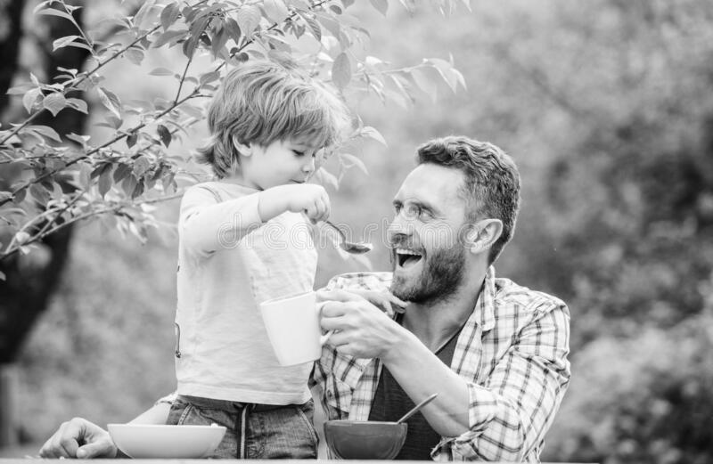 Feeding baby. Menu for children. Family enjoy homemade meal. Father son eat food and have fun. Food habits. Little boy royalty free stock image