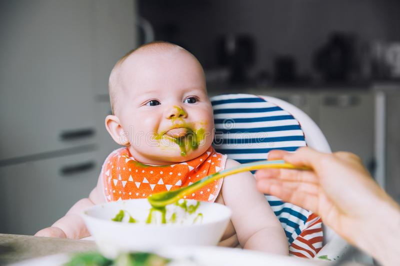 Feeding. Baby& x27;s first solid food. Feeding. Messy smiling baby eating with a spoon in high chair. Baby& x27;s first solid food. Mother feeding little child stock photos