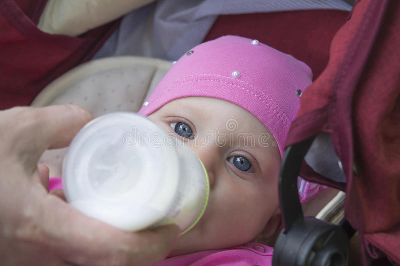 Feeding baby. Feeding the baby in the stroller for a walk royalty free stock photography