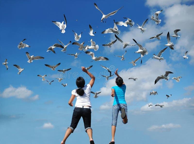 Feeding the Birds. Girls feeding a flock of birds (seagulls) flying in the air