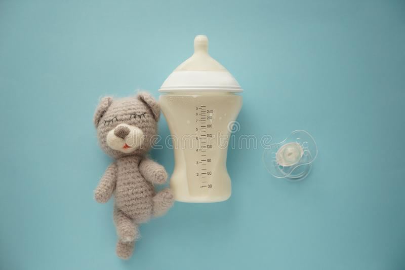 Feeding bottle of baby formula with pacifier and toy on color background stock images