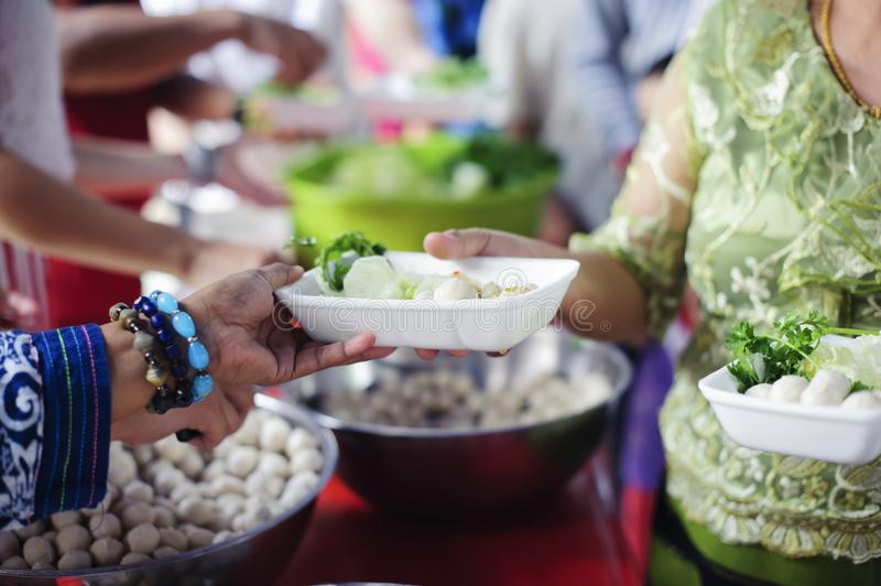 Feeding Concepts : Hand offered to donate food from a rich man Share : The concept of social sharing : Poor people receiving food. From donations royalty free stock image