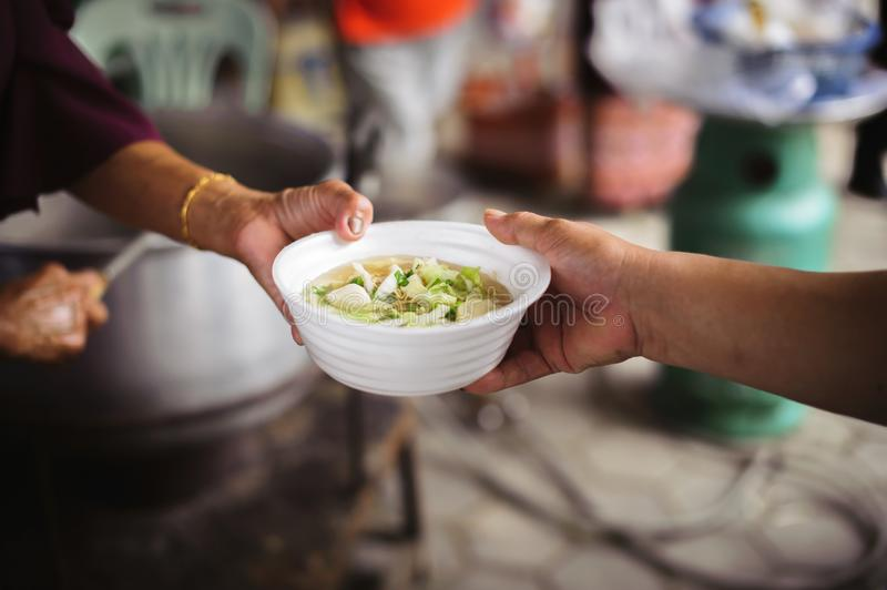 Feeding Concepts : Hand offered to donate food from a rich man Share : The concept of social sharing : Poor people receiving food. From donations stock photo