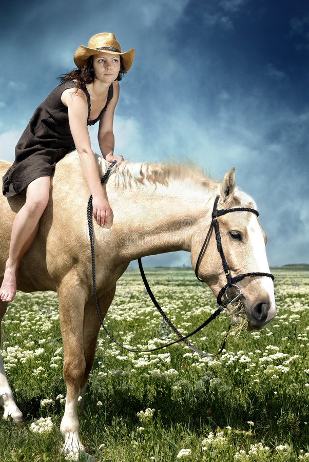 Feeding of the horse. Portrait of the woman feeding her horse with grass stock photography