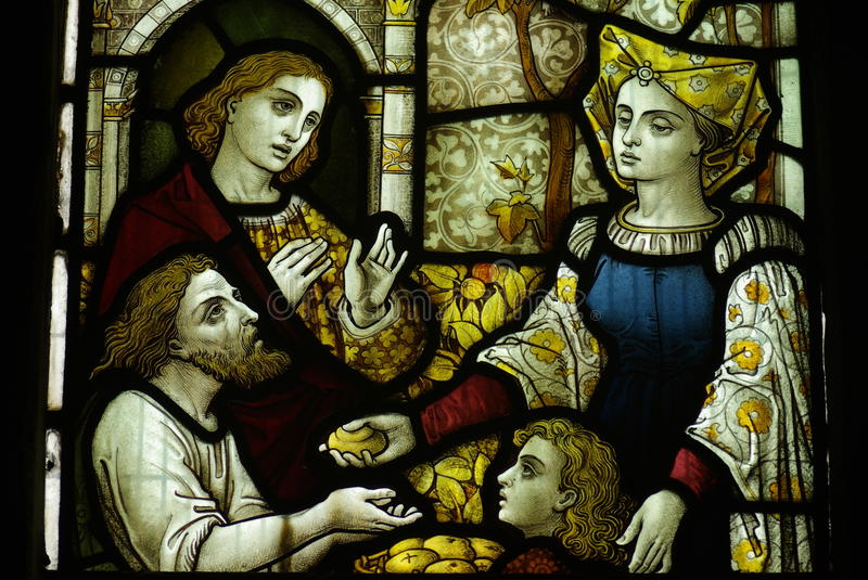 Feeding the poor (good deed) in stained glass. A photo of Feeding the poor (good deed) in stained glass royalty free stock photos