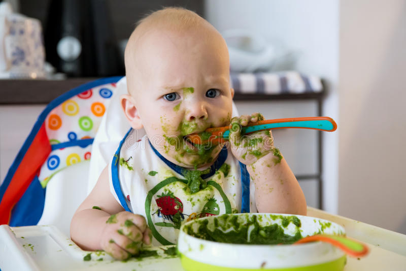 feeding Primer alimento sólido del bebé fotos de archivo