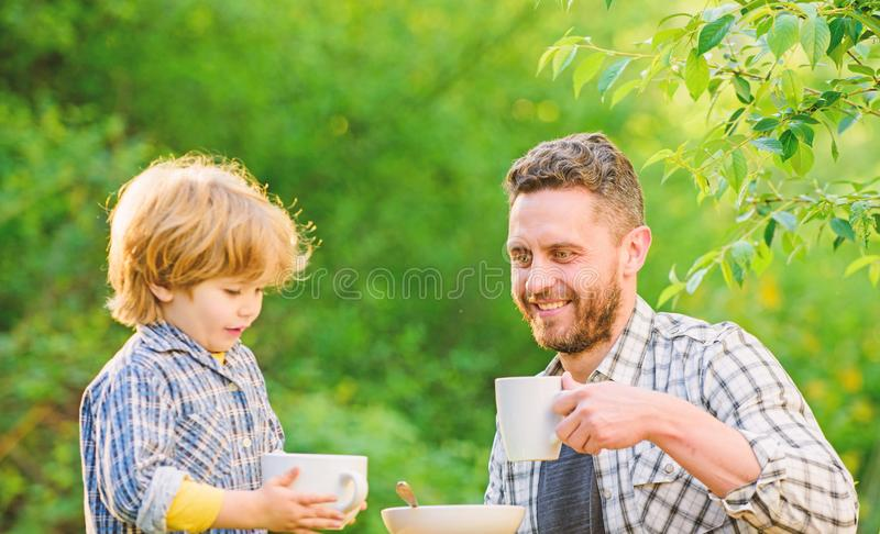Feeding son natural foods. Healthy food. Father and boy drink tea outdoors. Develop healthy eating habits. Feed baby royalty free stock images