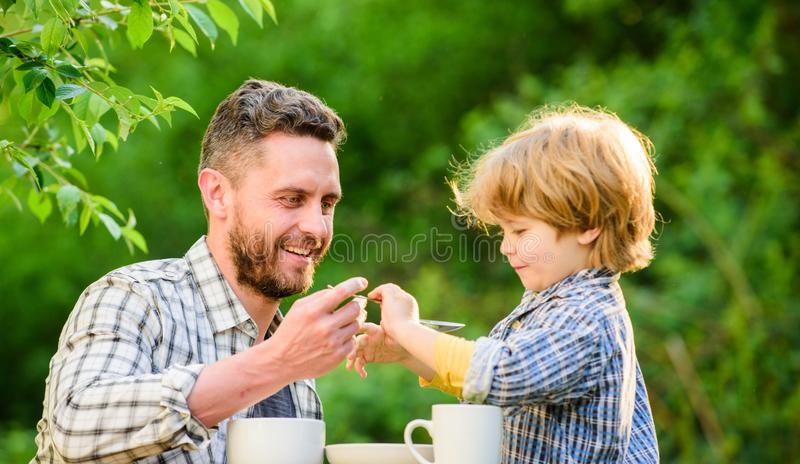 Feeding son natural foods. Stage of development. Feed son solids. Dad and boy eat and feed each other outdoors. Ways to stock image