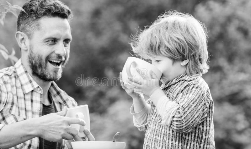 Feeding son natural foods. Stage of development. Healthy food. Dad and boy eat and feed each other outdoors. Ways to stock image