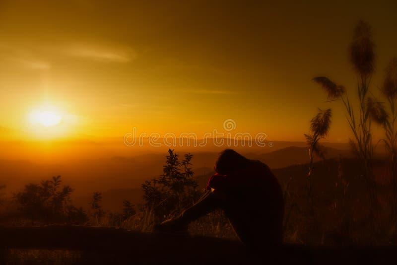 Feeing молодой женщины силуэта захода солнца унылый стоковое фото rf