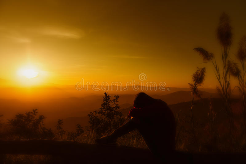 Feeing de jeune femme de silhouette de coucher du soleil triste photo libre de droits