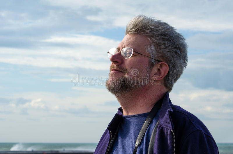 Man Feel the breeze. A silver haired man smiles as he feels the breeze stock image