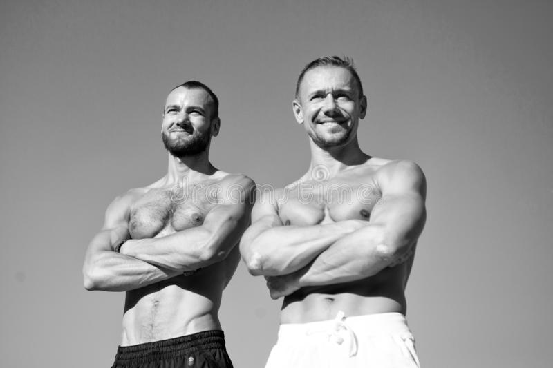Feel confidence. Guys muscular belly posing. Sport and bodycare. Muscular masculine guys look confident. Men royalty free stock images