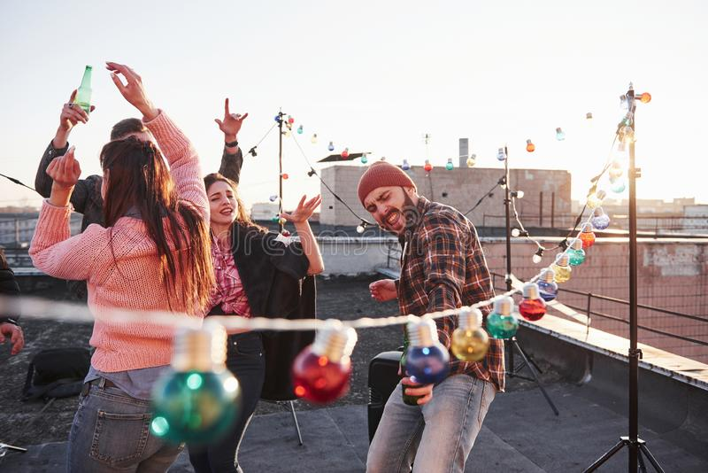 Feel the music. Singing favourite songs on the roof with friends and alcohol in hands stock photography