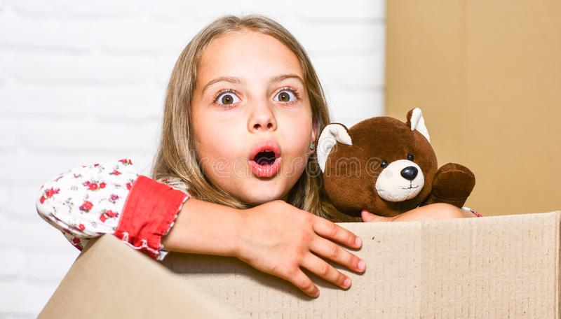 Feel of surpise. Cardboard boxes - moving to new house. repair of room. new apartment. happy little girl with toy royalty free stock photography