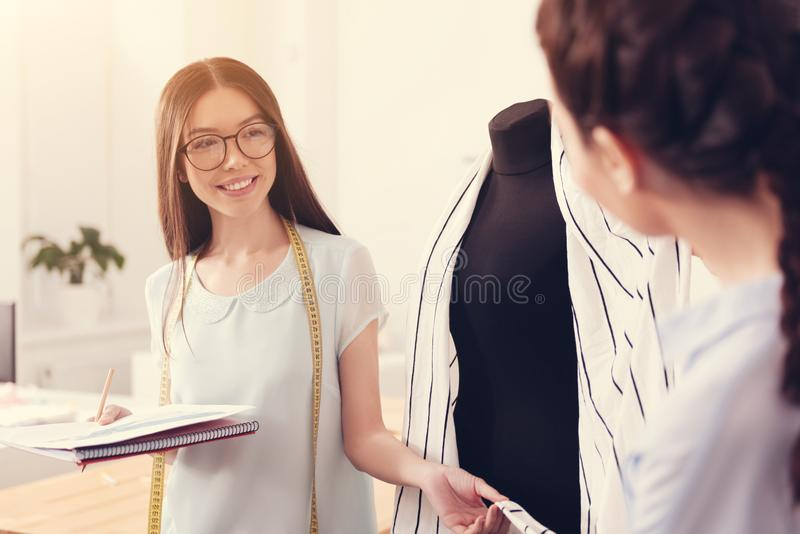 Cheerful dressmaker consulting the customer. Feel the texture. Waist up of young cheerful dressmaker holding a notebook while demonstrating high quality of royalty free stock photo