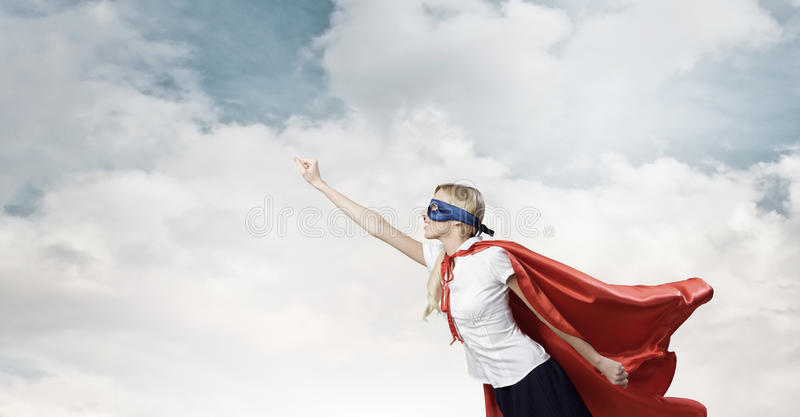 Feel yourself a hero!. Young confident woman in super hero costume royalty free stock image