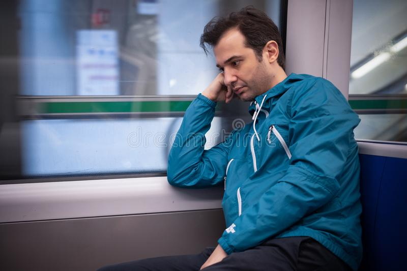 Feeling alone during travel in metro underground. Sleepy young man feeling sad in the train in the morning royalty free stock photo