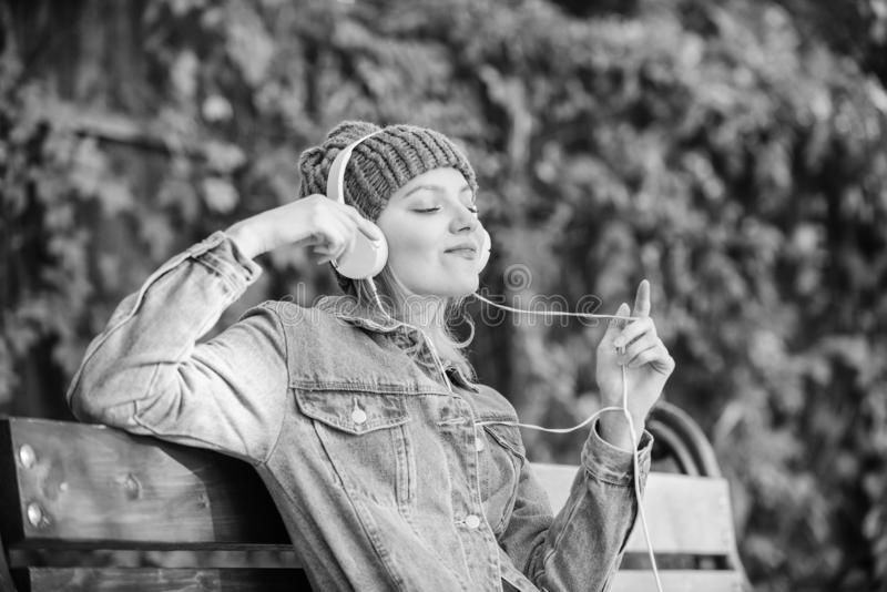 Feeling awesome. Cool funky girl enjoy music in headphones outdoor. Girl listen music in park. Melody sound and mp3. Music fan concept. Headphones must have stock photos
