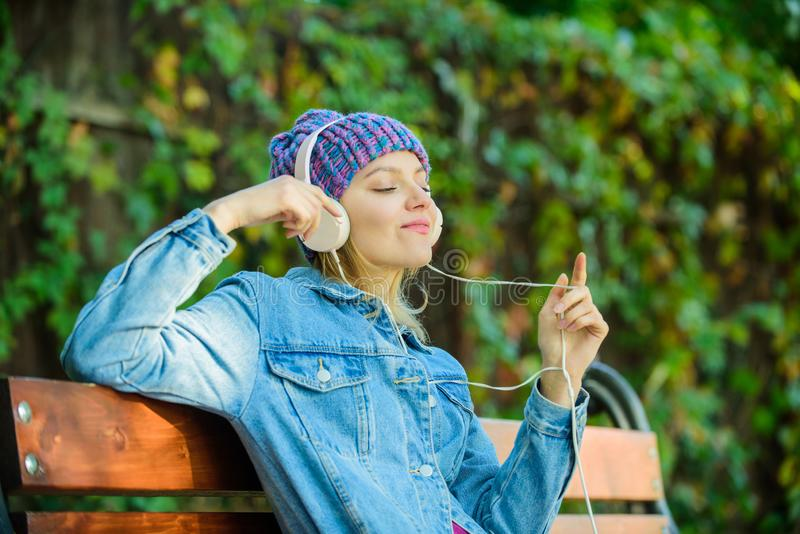 Feeling awesome. Cool funky girl enjoy music in headphones outdoor. Girl listen music in park. Melody sound and mp3. Music fan concept. Headphones must have royalty free stock image