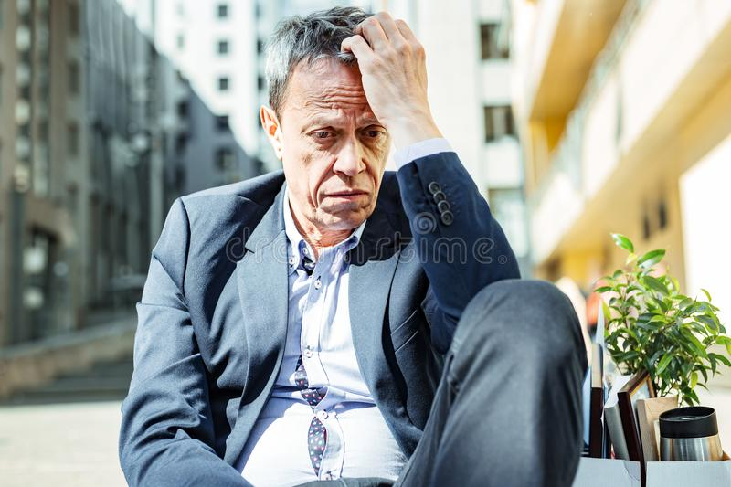 Wrinkled elderly man feeling awful after dismissal. Feeling awful. Wrinkled elderly experienced businessman feeling unbelievably awful after unexpected dismissal royalty free stock image