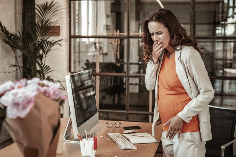 Long-haired expecting woman closing her mouth because of strong nausea royalty free stock photo