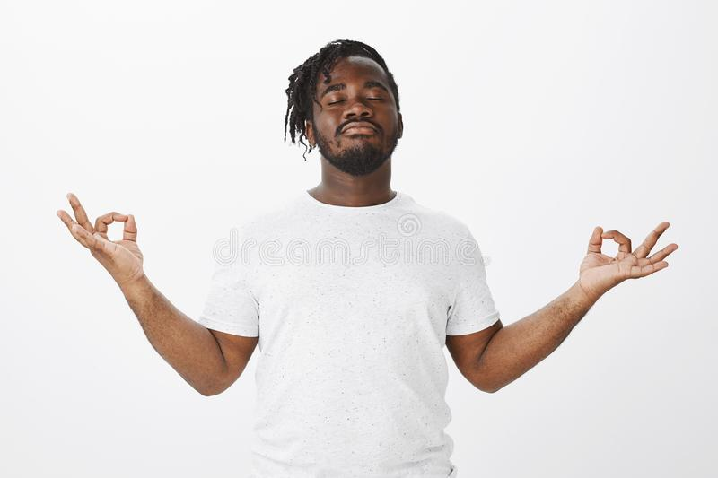 Feeling calm and relieved after meditation. Portrait of confident happy african-american boyfriend in casual outfit stock images