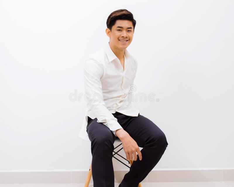 Feeling comfortable anywhere. Handsome young man looking at camera with smile while sitting against white background stock images