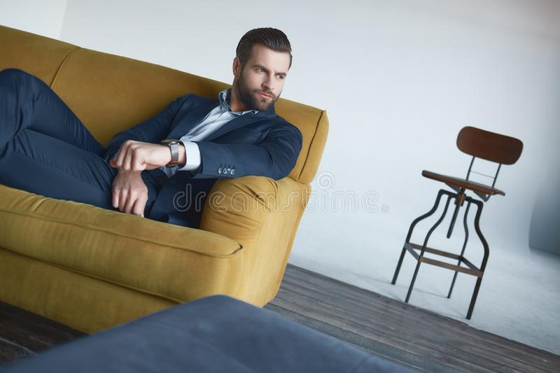 Feeling comfortable at office. Handsome and stylish businessman is sitting on sofa and thinking about something with. Fashion look. Serious businessman stock photography