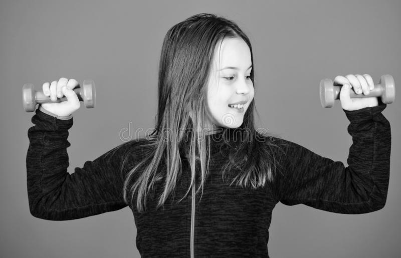 Feeling energy inside. Happy child with barbell. Fitness for energy health. workout of small girl hold dumbbell. weight. Lifting for muscules. Sport success royalty free stock photography