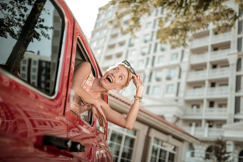 Cheerful woman leaning out of the car window. royalty free stock photos