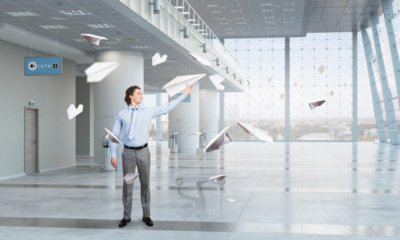 Feeling free and careless. Young businessman in modern office interior playing with paper plane stock photo