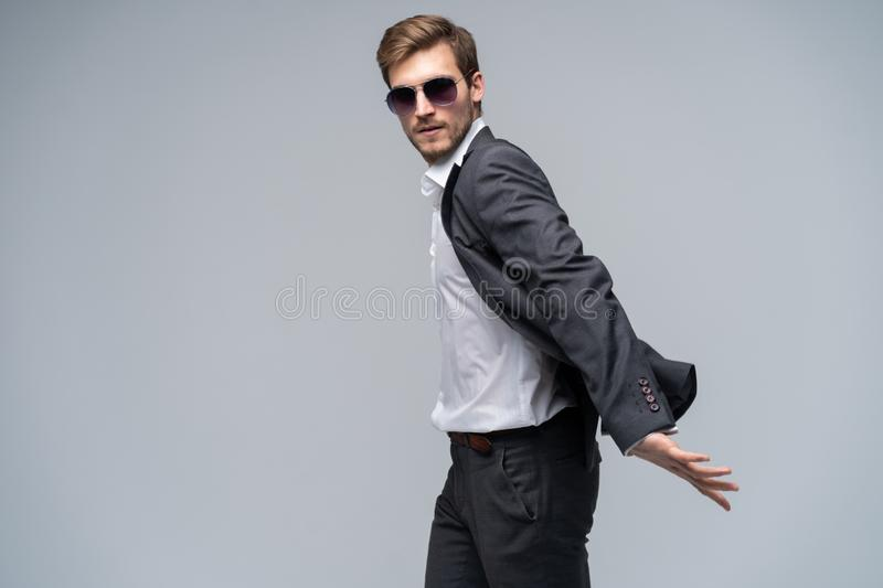 Feeling free and comfortable in his style. Handsome young man in full suit and sunglasses moving in front of gray royalty free stock images
