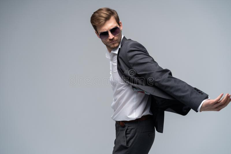 Feeling free and comfortable in his style. Handsome young man in full suit and sunglasses moving in front of gray stock photos
