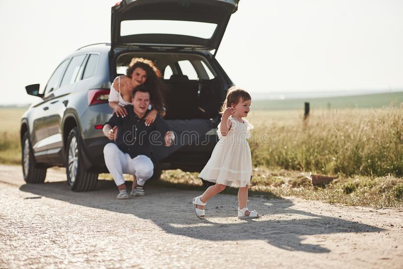 Feeling free. Family have some good time at countryside near silver automobile at sunset stock image