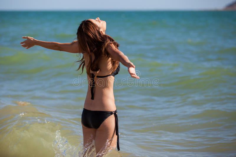 Feeling free in the ocean. Cute girl raising her arms and enjoying the sun and the ocean stock images