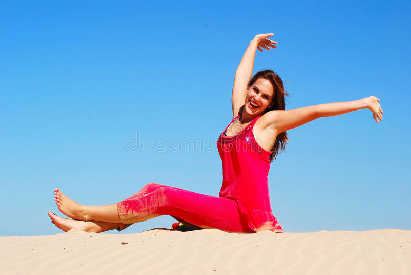 Feeling great - feeling happy. A beautiful young Caucasian woman in pink clothes with happy smiling facial expression sitting on a lonely sand dune in front of