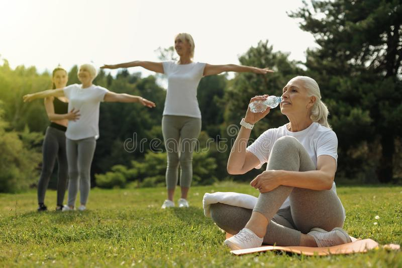 Active retired lady drinking water after intensive workout stock photography