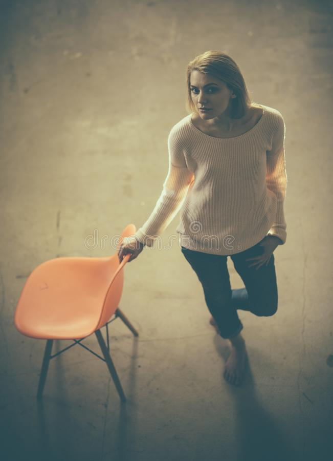 Feeling hopeless or lonely and depressed. thoughtful woman at home with orange chair. lazy day at home. Frustrated woman. Standing and looking away up. home stock image