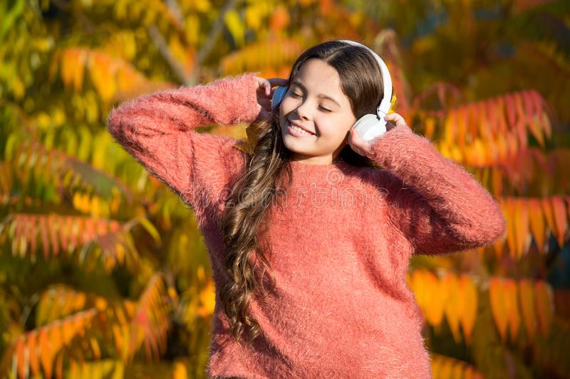 Feeling inspired with favorite song. little child in headset. enjoy autumn day. good day for park walk. she love nature. And music. feel real joy. fall mood stock photos