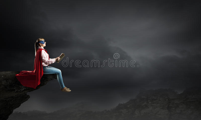 Feeling like super woman. Young woman in super hero costume reading book royalty free stock photo