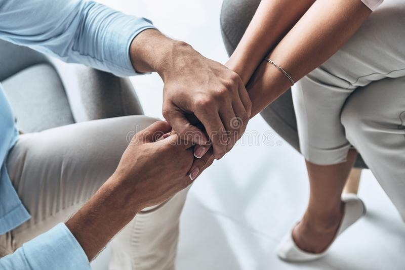 Feeling loved. Close up top view of young couple holding hands while sitting indoors royalty free stock image