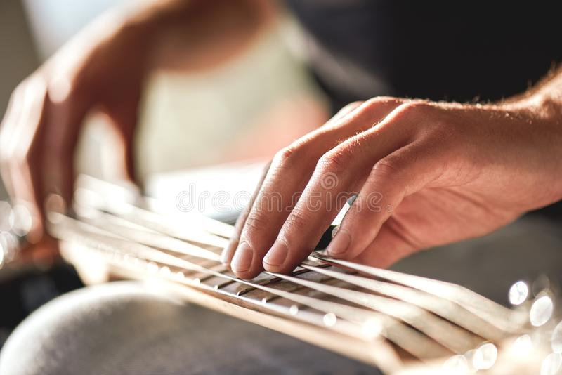 Feeling my instrument...Close-up of male hands touching metal strings of guitar stock image