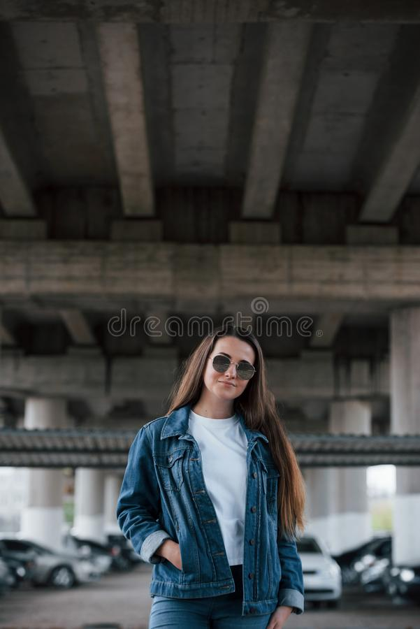 Feeling nice. Portrait of beautiful young woman standing under the bridge outdoors royalty free stock images